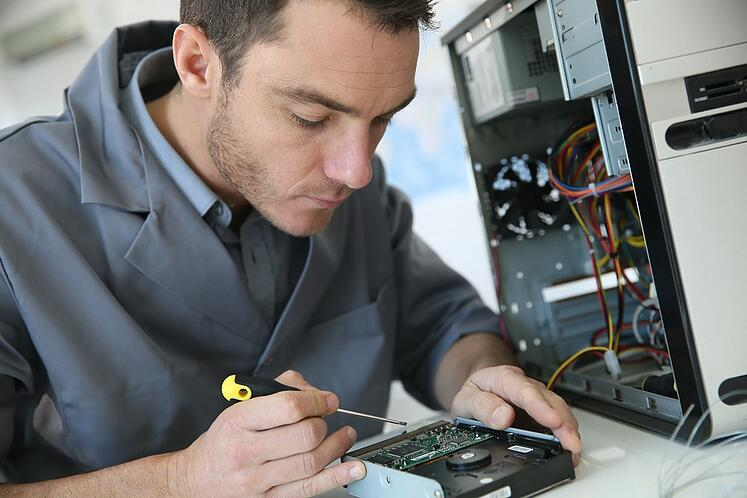 Technician fixing computer hardware.jpeg
