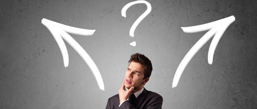 Young businessman taking a decision with arrows and question mark above his head-038884-edited.jpeg